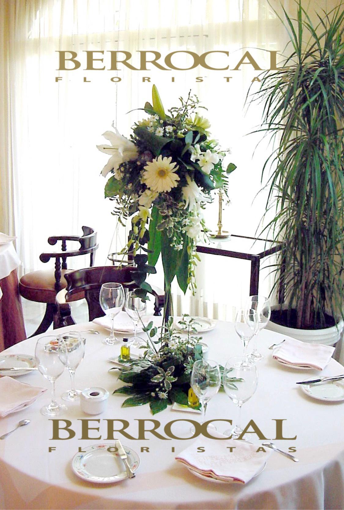Centro de mesa bajo, blanco.  Velas especiales. Longiflorum. Margarita. Orquídea Dendrobium. Crisantemos bola.  Verdes, hojas de Aralia. Grass