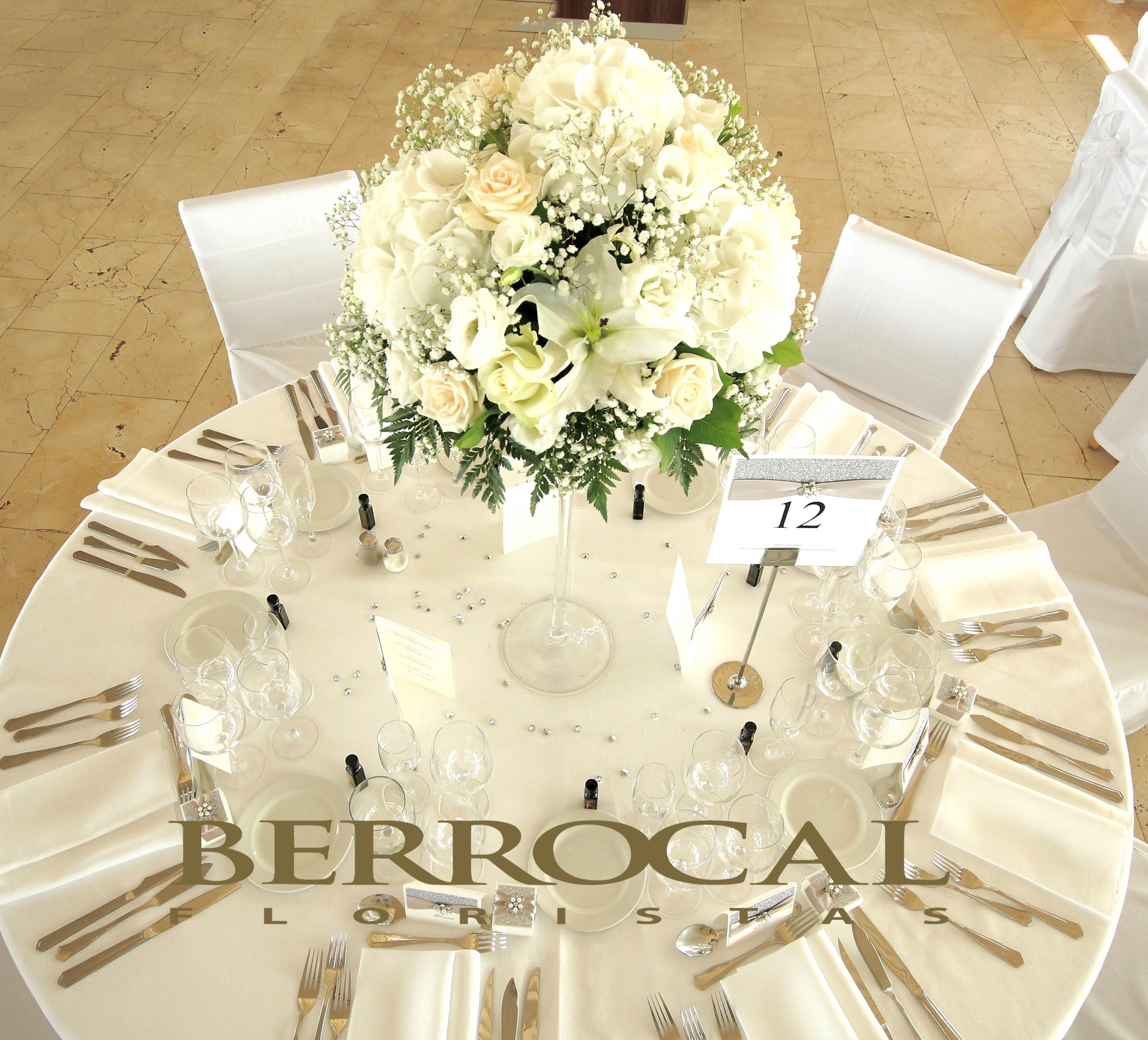 Central piece.  Martini glass.  Hydrangeas, roses, Lilium, lisianthus. White and Ivory colors.