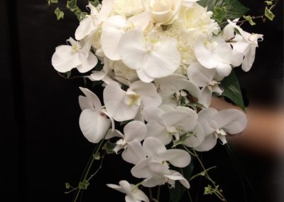 Gorgeous bridal bouquet in a traditional all white cascade style. With phalaenopsis orchids, roses, ivy.