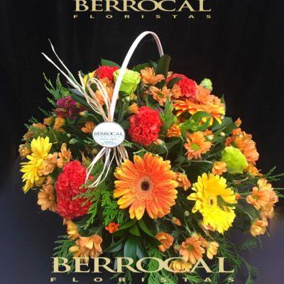 Cesta con flores variadas, tonos anaranjados.