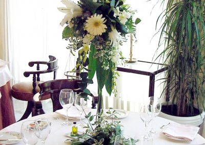 Low centerpiece, white. Special candles. Longiflorum Daisy flower. Dendrobium orchid. Chrysanthemums ball. Greens, leaves of Aralia. Grass.