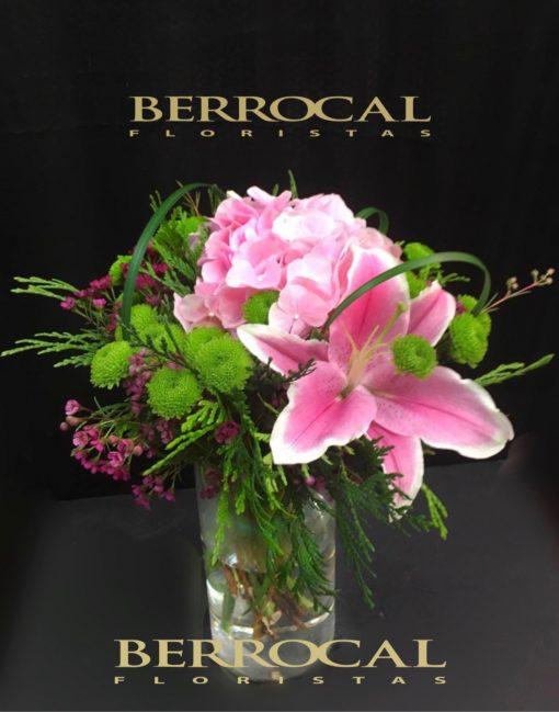 Arreglo de flores, colores rosados y verdes, en vaso de cristal.