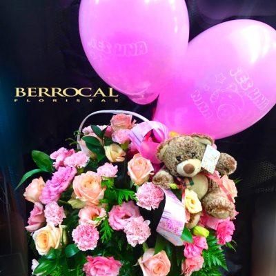 Cesta de flores rosadas, con peluche y globos.