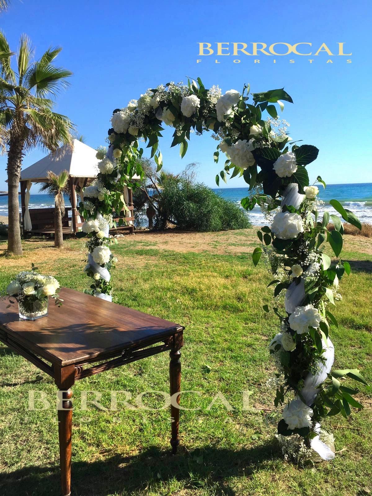 Arco blanco,con verdes, flores y tul blanco Y Composición coordinada de rosas blancas en cristal, mesa Ceremonia Boda.